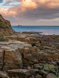 North Sea Coast in Cullercoats Bay, England, UK. Evening Clouds and cliffs on the North Sea Coast in Cullercoats Bay, Tyne And Wear, England, UK - with a ship stock photos