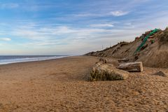 North Sea coast in Newport, Norfolk, England, UK. The empty beach with some wind turbines in the background royalty free stock image