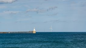 North Sea Coast at the South Beach in Blyth, England, UK. Blyth Lighthouse, the pier and a wind turbine on the North Sea Coast, seen on South Beach in Blyth royalty free stock photography