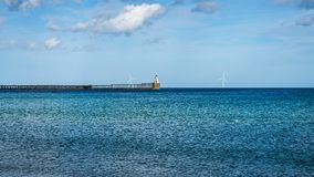 North Sea Coast at the South Beach in Blyth, England, UK. Blyth Lighthouse, the pier and a wind turbine on the North Sea Coast, seen on South Beach in Blyth stock photo