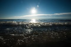 Atmospheric backlight photo of the sea with rippling water that. North Sea coast with splashing drops and wavy water on a summer day long the Dutch coast royalty free stock images