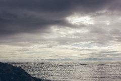 North sea with cold and snow view of the horizon and rocky coast royalty free stock images