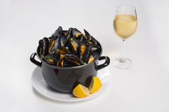 North Sea fresh steamed mussels, tasty seasonal food with lemon. North Sea fresh steamed mussels in black pan, tasty seasonal food with lemon Stock Photography
