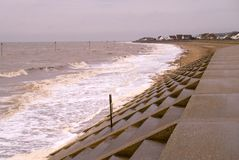 Windy day on Heacham`s north promenade. The north sea rolling into Heacham`s north promenade sea defence`s on a windy winter`s day stock photo