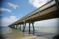 North Side of Deerfield Beach Pier. This is the north side of the Deerfield Beach, Florida fishing pier with swimmers out in the Atlantic ocean to the left and stock image