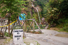 North Sikkim Highway. A milestone beside the bridge crosses over the stream as a part of North Sikkim Highway at Menrong Gong on the way from Gangtok to Mangan Royalty Free Stock Photo