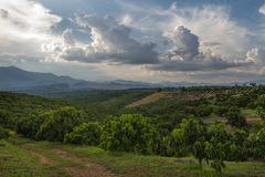 North Thailand landscape with mountain and longan fields with amazing cloudy sky and beautiful light. North Thailand landscape with path, mountain and longan stock image