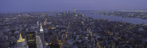 This is the north to south view of New York City from the Empire State Building. The lights of the skyscrapers are on as it dusk. Royalty Free Stock Photo