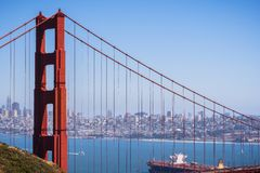 The north tower of Golden Gate Bridge; San Francisco`s skyline visible in the background; large cargo ship passing under the. Bridge royalty free stock photos