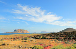 North-West of Graciosa, Canary Islands. North-Western edge of Island Graciosa with an ancient volcano on the right and Island Montana Clara across the water Royalty Free Stock Photo