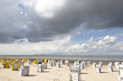 Northern coast with beach chairs. Northern coast at the location of  Cuxhaven with beach chairs and cloudy sky Royalty Free Stock Image