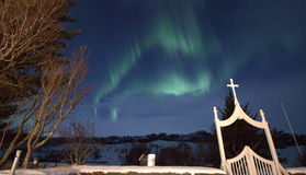 Northen light above cemetery. Light aurora borealis appeares above our heads in Iceland Royalty Free Stock Photos