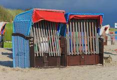 Norther Beach Chairs on the island of Foehr. Two colorful northern beach chairs on the German North Frisian island of Foehr Föhr in front of a dark sky Stock Photography