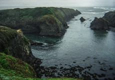Northern California coastal cliffs with moody atmosphere at Mendocino. Beautiful landscape of a foggy summer morning on Mendocino, California coast. Calm waves Royalty Free Stock Photo