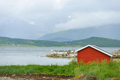 Northern landscape with red house on background of picturesque mountains Royalty Free Stock Photo
