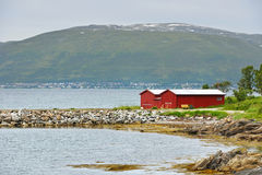 Northern landscape with red house on background of picturesque mountains. Tromso Royalty Free Stock Image
