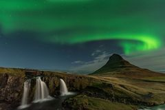 The Northern Light at the mountain Kirkjufell Iceland. Landscape of waterfall Kirkjufellsfoss, with green bands of Aurora Borealis. Snaefellnes, Iceland stock photo