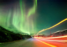Northern Light Trails. The Northern Lights in Norway landscape with red light trails on a road Stock Image