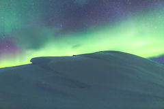 Northern light (aurora borealis) behind a snowy hill Stock Photos