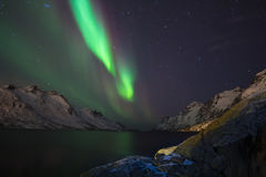 Northern light (aurora borealis) in a narrow fjord with white mountains Royalty Free Stock Photos