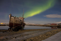 Northern light (aurora borealis) over an abandoned boat Royalty Free Stock Images