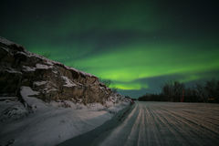Northern light (aurora borealis) over an icy snowy road Royalty Free Stock Photo