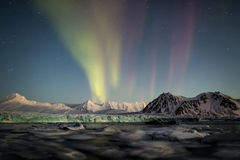 Northern Lights above the Arctic glacier and mountains - Svalbard, Spitsbergen Stock Image