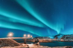 Northern lights above bridge with illumination in Norway. Northern lights above bridge with illumination in Lofoten islands, Norway. Aurora borealis. Starry sky royalty free stock images