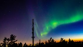 Northern lights above the city lights with transmitter. This night photography shows northern lights and starry sky in Lapland above the city of rovaniemi in stock photography