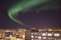 Northern lights above the city of Tromso. Green northern lights above the city of Tromso in Norway stock photography