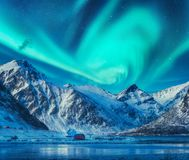 Northern lights above snowy mountains, frozen sea coast. And houses in Lofoten islands, Norway. Aurora borealis and small village. Winter landscape with polar stock photography