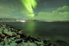 Northern lights, aurora borealis, above a fjord surrounded by a Stock Images