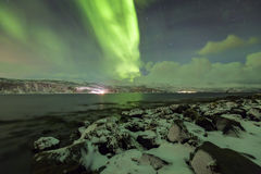 Northern lights, aurora borealis, above a fjord surrounded by a Royalty Free Stock Image