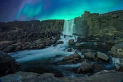 Northern lights/aurora borealis are dancing over the famous oxarafoss waterfall at night in thingvellir