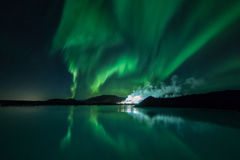 Northern Lights. Or Aurora Borealis dancing in the sky with its reflection dancing on the surface of the Blue Lagoon, Iceland Stock Photo