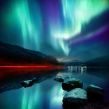 Northern Lights & x28;aurora borealis& x29;. A large Northern Lights & x28;aurora borealis& x29; display glowing over a mountain pass and reflected on a lake at Royalty Free Stock Image