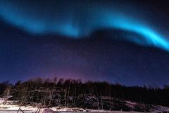 Northern lights aurora borealis in Lofoten islands, Norway. Night winter landscape. With polar lights and beautiful starry sky Stock Photos