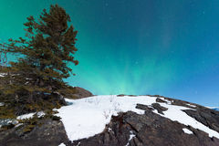 Northern Lights Aurora borealis over snowy rocks Royalty Free Stock Image