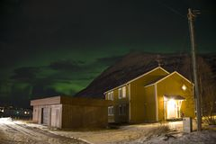 The northern lights aurora borealis seen behind a home in a small village in the north of Norway. In the middle of winter. The northern lights aurora borealis stock photo