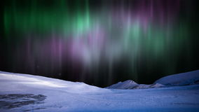 Northern Lights aurora Borealis in the snowy mountains.
