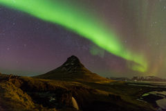 Northern lights or Aurora dancing with fully of stars on the sky of Iceland mountain landscape. Royalty Free Stock Images