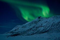 Northern Lights behind a mountain. Aurora Borealis curls in the arctic sky behind a mountain. Norway, tromso Stock Photo