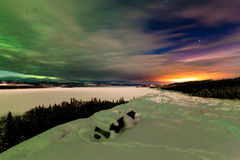 Northern Lights and city light pollution night sky. Spectacular view from snow-covered bench: Northern Lights or Aurora borealis clouds and light pollution from stock photography