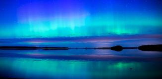 Northern lights dancing over calm lake aurora borealis Royalty Free Stock Image