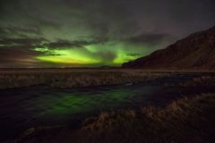 Aurora Borealis reflecting in a stream in Iceland. Northern Lights down stream from Seljalandsfoss waterfall in South Iceland Royalty Free Stock Photos