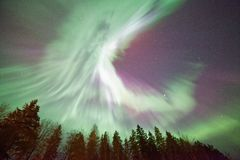 Northern lights and  green aurora corona in the cold winter sky. Stock Image