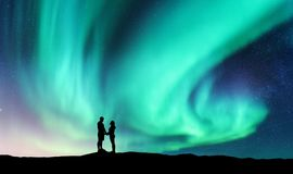 Northern lights and hugging couple on the hill Stock Photo