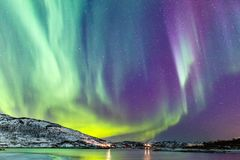 Northern lights. Incredible Northern lights Aurora Borealis activity above the coast in Norway stock photography
