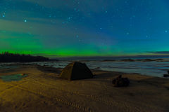 Northern Lights in night sky. Over lake with tent in foreground Royalty Free Stock Image