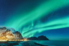 Northern lights in Lofoten islands, Norway. Green Aurora borealis. Starry sky with polar lights. Night winter landscape with aurora, sea with sky reflection stock image